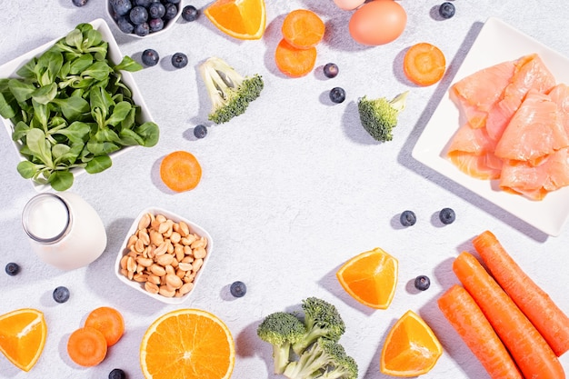 Lebensmittel, die helfen, die augen gesund zu erhalten, produkte zur erhaltung einer guten sehkraft, vitamine für die augen. schwarzes brett mit kopienraum, auswahl an lebensmitteln für die augengesundheit auf konkretem hintergrund, flache lage, draufsicht