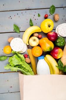 Lebensmittel einkaufen . unterschiedliche lebensmittelpapiertüte auf hölzernem. flach liegen.