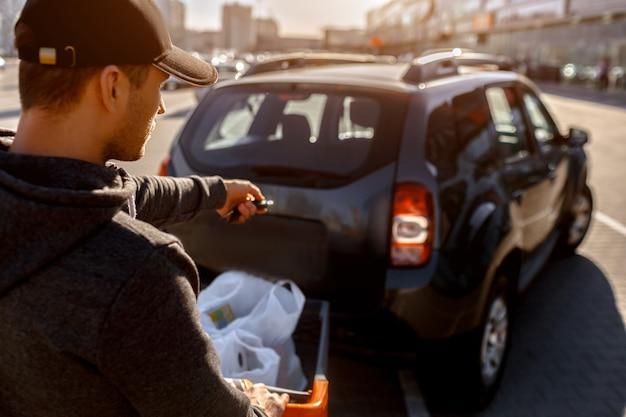 Lebensmittel in einem supermarkt kaufen. einkaufen ein junger mann kauft eine woche lang essen in einem großen einkaufszentrum auf dem land. faltet taschen mit gemüse, obst, fleisch und milchprodukten auf einem parkplatz