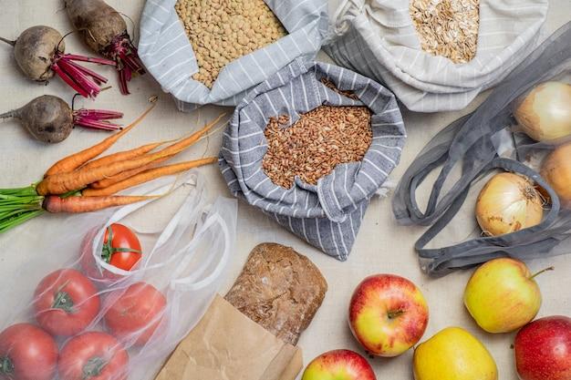 Lebensmittel in wiederverwendbaren beuteln auf naturflachs oder hanf, draufsicht. konzept des null-abfall-ethischen einkaufens