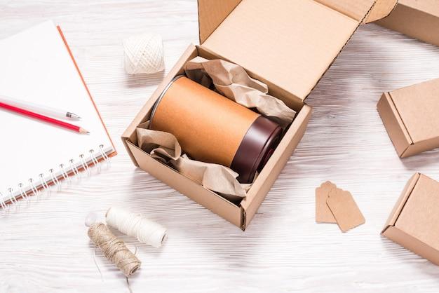 Lebensmittel können in pappkarton auf holzschreibtisch verpackt werden