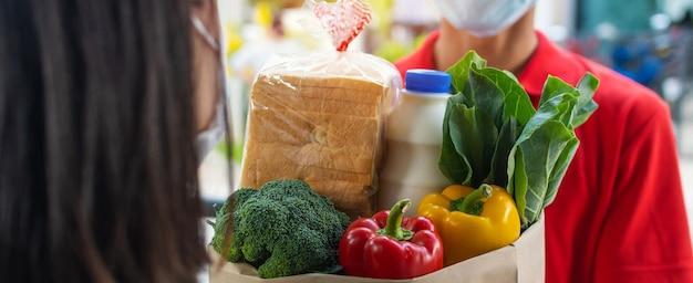 Lebensmittel-lieferservice-mann, der schutzgesichtsmaske trägt, die frische lebensmittel-set-tasche übergibt