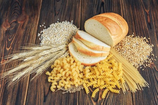 Lebensmittel mit hohem kohlenhydratgehalt auf hölzernem hintergrund. laib, nudeln, perlgerste und hafer.