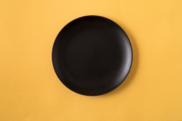 Lebensmittel mit leerer schwarzer platte, über gelber, flacher lage.