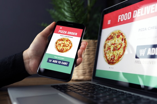 Lebensmittel-online-bestell- und liefer-app auf laptop- und telefonbildschirmen, mann bei der arbeit, geschäftsbürohintergrund. anwendung für den lieferservice von speisen zum mitnehmen