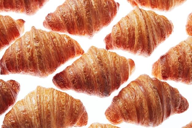 Lebensmittel-rautenmuster von knusprigen hausgemachten französischen croissants auf einem hellen hintergrund. nahaufnahme.