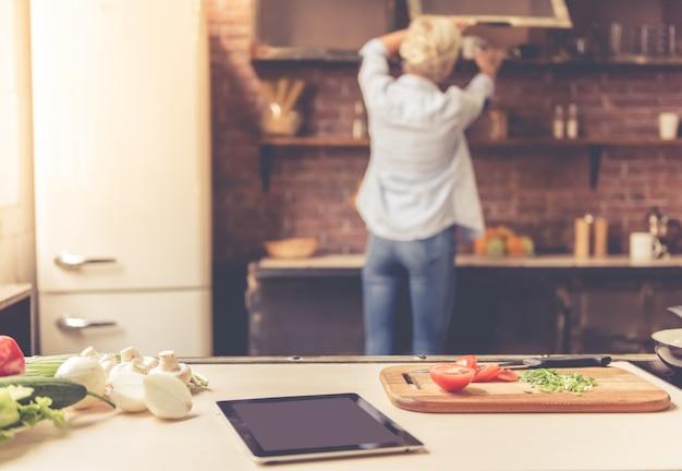 Lebensmittel und digitale tablette auf küchentisch.