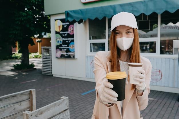 Lebensmittel- und getränkeunternehmen während der coronavirus-pandemie kaffee zum mitnehmen in weiblichen händen in die tasse