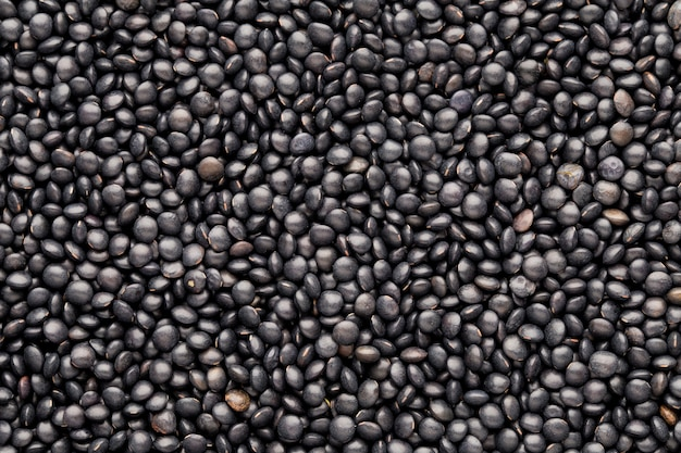 Lebensmittel- und kochhintergrund von gesunden getrockneten schwarzen linsen.