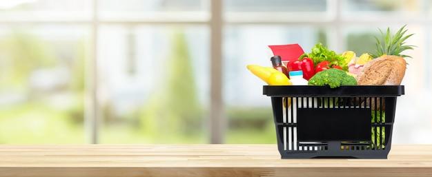 Lebensmittel und lebensmittelgeschäfte im einkaufskorb auf küchentischfahnenhintergrund