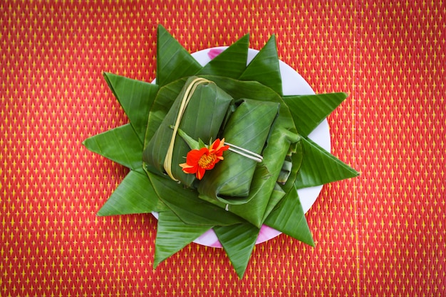 Lebensmittel und nachtisch thailändisch eingewickelt im bananenblatt auf platte