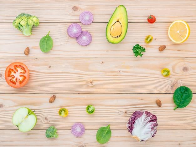 Lebensmittel- und salatkonzept mit der ebene der rohen bestandteile legen auf hölzernes.