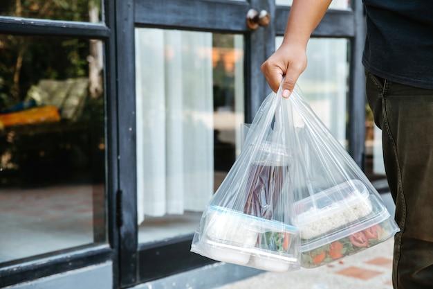 Lebensmittelboxen in plastiktüten werden vom zusteller zu hause an den kunden geliefert