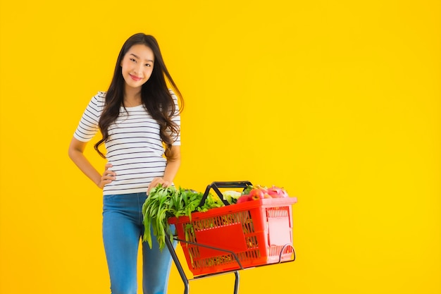 Lebensmitteleinkauf der jungen asiatischen frau vom supermarkt und vom wagen