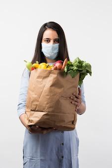 Lebensmitteleinkauf in pandemie - hübsche indische junge frau, die während der virusepidemie eine schutzmaske trägt, während sie eine papiertüte mit gemüse und obst hält
