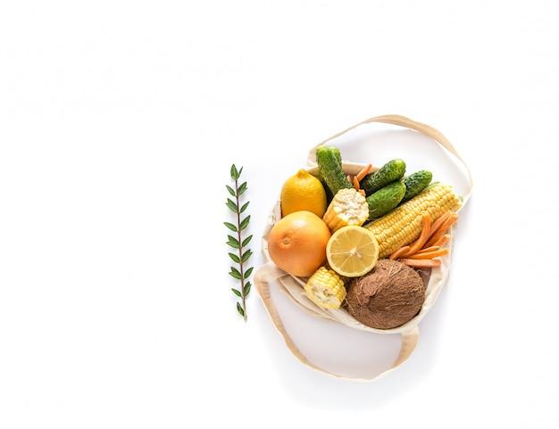 Lebensmitteleinkauf mit öko-tasche über weißer wand. null abfall und plastikfreies konzept. flach liegen. speicherplatz kopieren.