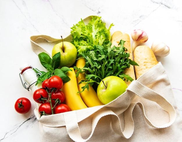 Lebensmitteleinkauf ohne abfall. öko-naturtasche mit obst und gemüse, umweltfreundlich, flach gelegt.