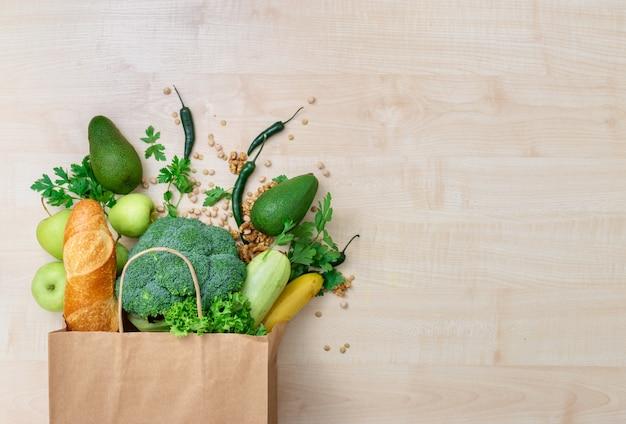 Lebensmitteleinkaufstasche mit gesundem lebensmittel auf einer hölzernen draufsicht