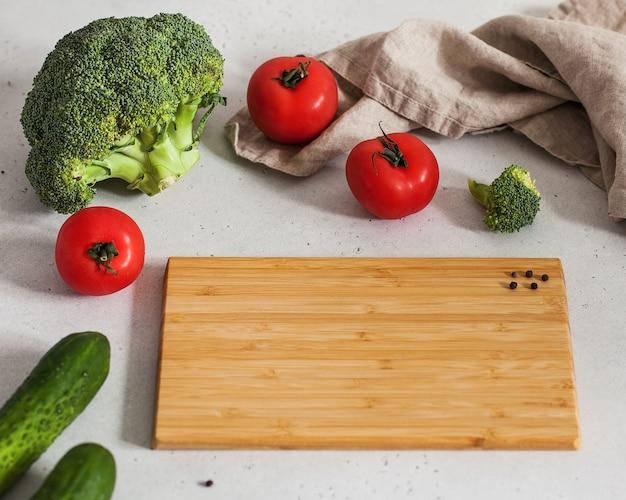 Lebensmittelfoto mit leerem schneidebrett für text mit tomaten, brokkoli und gurken