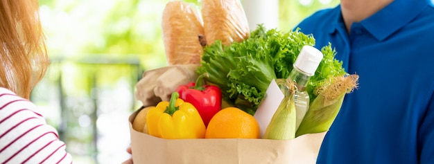 Lebensmittelgeschäft-lieferbote in blauer uniform, die lebensmittel an eine kundin zu hause liefert, bannergröße