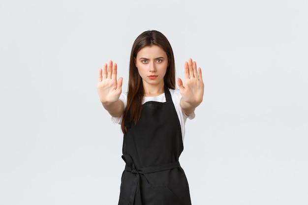Lebensmittelgeschäft-mitarbeiter, kleinunternehmen und cafés-konzept. ernsthafte junge caféarbeiterin in schwarzer schürze streckt die hände aus, um stopp- oder verbotsgesten zu zeigen, weißer hintergrund.