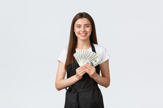 Lebensmittelgeschäft mitarbeiter, kleinunternehmen und coffeeshops konzept. aufgeregte fröhliche junge weibliche barista verdienen viele tipps, haben geld, um sommerferien zu reisen, lächeln glücklich, stehen weißen hintergrund
