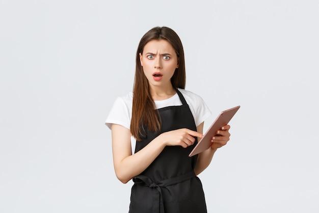 Lebensmittelgeschäft mitarbeiter, kleinunternehmen und coffeeshops konzept. verwirrte und enttäuschte kellnerin oder caféarbeiterin, die auf ein digitales tablet zeigt und einen fehler im cafébudget sieht