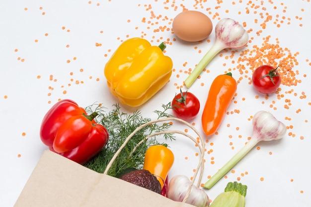 Lebensmittelgeschäft-set gemüse in papiertüte. pfeffer, knoblauch und rote linsen auf dem tisch. flach liegen. weißer hintergrund.