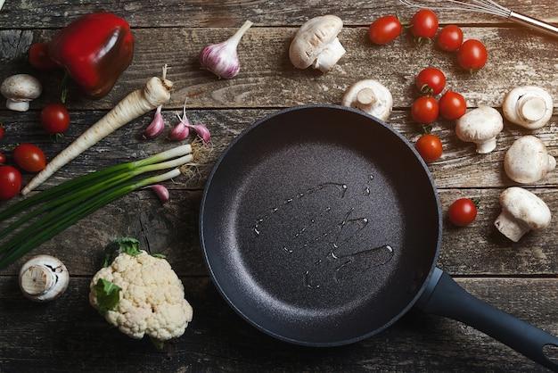 Lebensmittelhintergrund auf dunklem holztisch. zutaten zum kochen von speisen mit schwarzer pfanne. ansicht von oben, kopienraum. tomaten, zwiebeln, gewürze und kräuter umgeben leere pfanne.