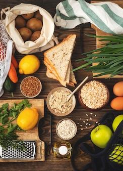 Lebensmittelhintergrund, gemüse, obst und getreide auf hölzernen, gesunden kochzutaten. draufsicht.