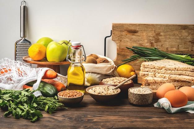 Lebensmittelhintergrund, gemüse, obst und müsli auf einem holztisch in der küche, gesunde kochzutaten.