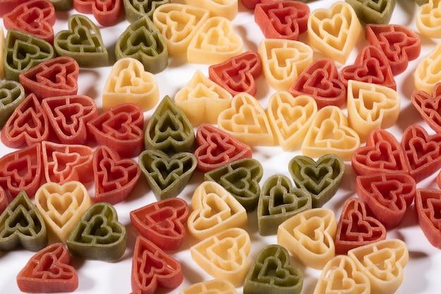 Lebensmittelhintergrund, italienische dreifarbige herzförmige nudeln.
