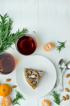 Lebensmittelhintergrund. kulinarischer hintergrund. kuchen auf einem weißen teller auf einem hellen hölzernen hintergrund. teeparty mit kuchen. esstisch. platz für text. speicherplatz kopieren.