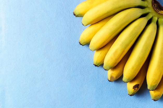 Lebensmittelhintergrund mit bananenfrucht auf blauem papier.