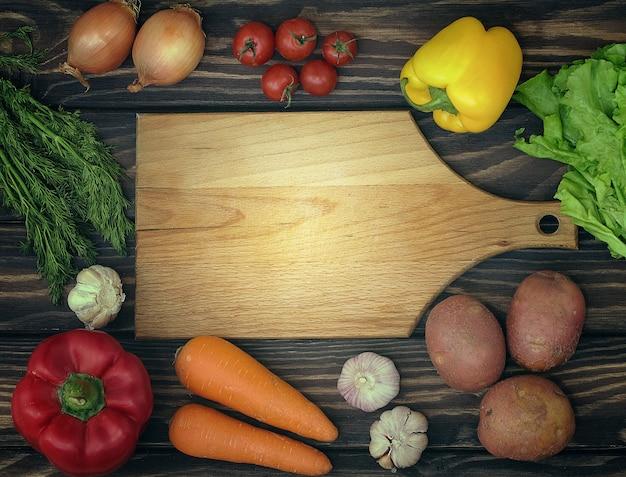 Lebensmittelhintergrund mit draufsicht des gemüses und des schneidebrettes