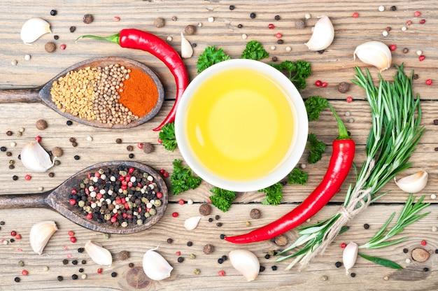 Lebensmittelhintergrund mit olivenöl, petersilie, rosmarin, pfeffer, paprika, bockshornklee, koriander, paprikas und knoblauch