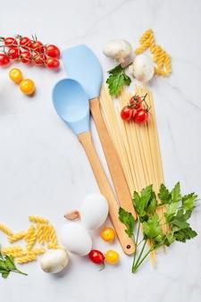 Lebensmittelhintergrund mit platz für text, mit verschiedenen arten von nudeln, tomaten, kräutern, pilzen, eiern, gewürzen auf hellem marmorhintergrund verstreut, draufsicht. italienisches küchenkonzept