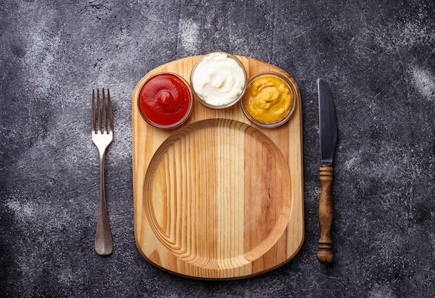 Lebensmittelhintergrund mit senf, ketchup, mayonnaise, gabel und messer. platz für text