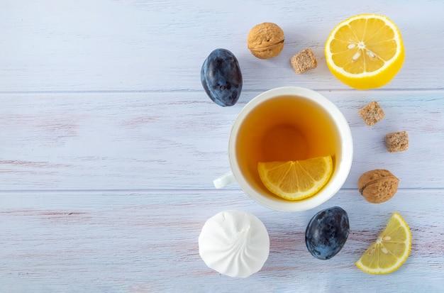 Lebensmittelhintergrund mit weißer porzellantasse tee, zitrone, pflaumen, nektarinen, walnüssen und marshmallow