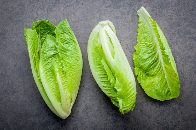 Lebensmittelhintergrund- und -salatkonzept mit frischer lattich flach legen sie auf dunklen steinhintergrund