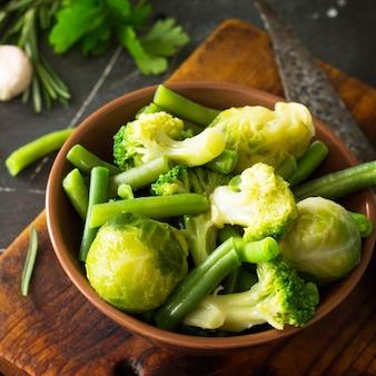 Lebensmittelhintergrund verschiedene grüne sommergemüse gewürze olivenöl und frische kräuter d