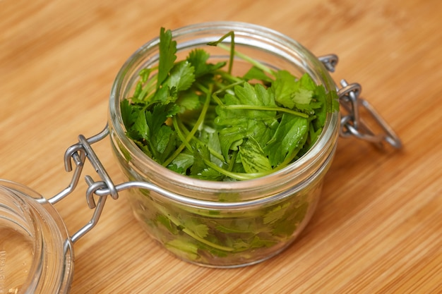 Lebensmittelinhaltsstoff, korianderblätter, frischer grüner koriander auf holzoberfläche