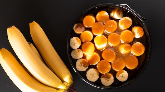Lebensmittelkonzept, das hausgemachte banoffee-torte des nachtischs auf schwarzem hintergrund macht