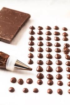 Lebensmittelkonzept, das selbst gemachte schokoladenchips für bäckerei auf weißem hintergrund macht