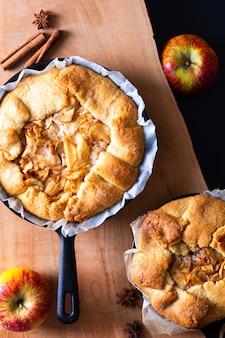 Lebensmittelkonzept frisch gebackene goldene selbst gemachte organische butterartige kruste apfel-galette-kuchens in der eisenbratpfannenwanne