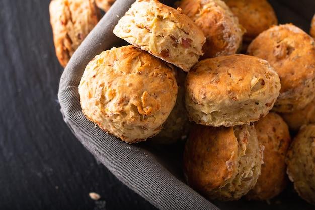 Lebensmittelkonzept frische gebackene selbst gemachte butterartige, salzige schinken- und käsescones auf schwarzem