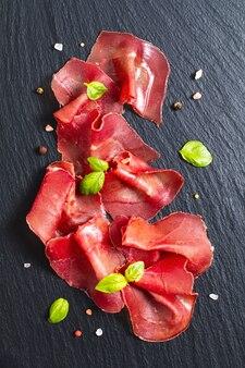Lebensmittelkonzept geschnittene getrocknete kurierte rindfleisch bresaola auf schwarzem schiefersteinbrett