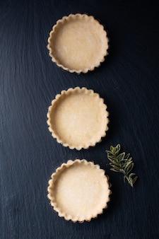 Lebensmittelkonzept hausgemachte leere tortenkruste für bio-zitrone, limettenkuchen oder minikuchen auf schwarzem schiefersteinbrett