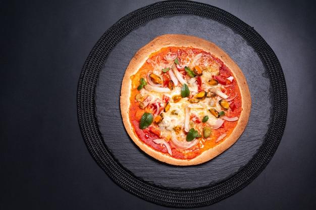 Lebensmittelkonzept hausgemachte tortilla-meeresfrüchte-pizza auf schwarzem schiefersteinteller