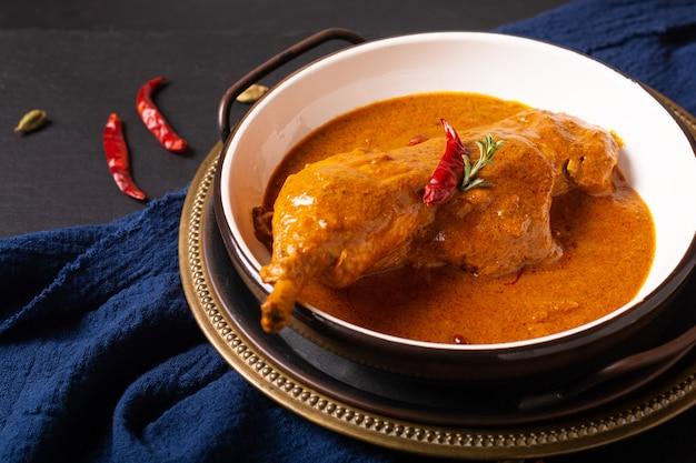 Lebensmittelkonzept hausgemachtes tikka masala huhn oder rotes curry auf schwarzem hintergrund